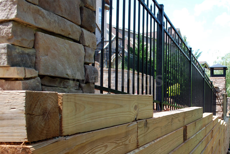 timber retaining wall with safety rails and stone pillars